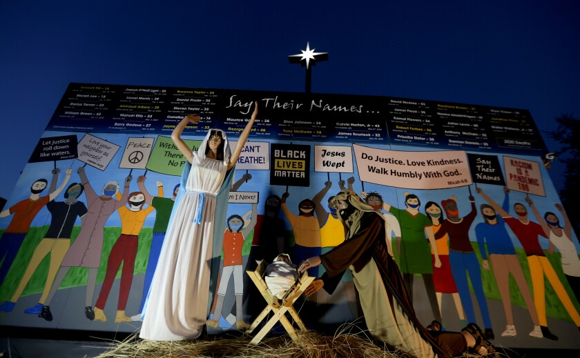 Claremont United Methodist Church's Nativity scene shows Mary, Joseph and baby Jesus in front of people wearing masks