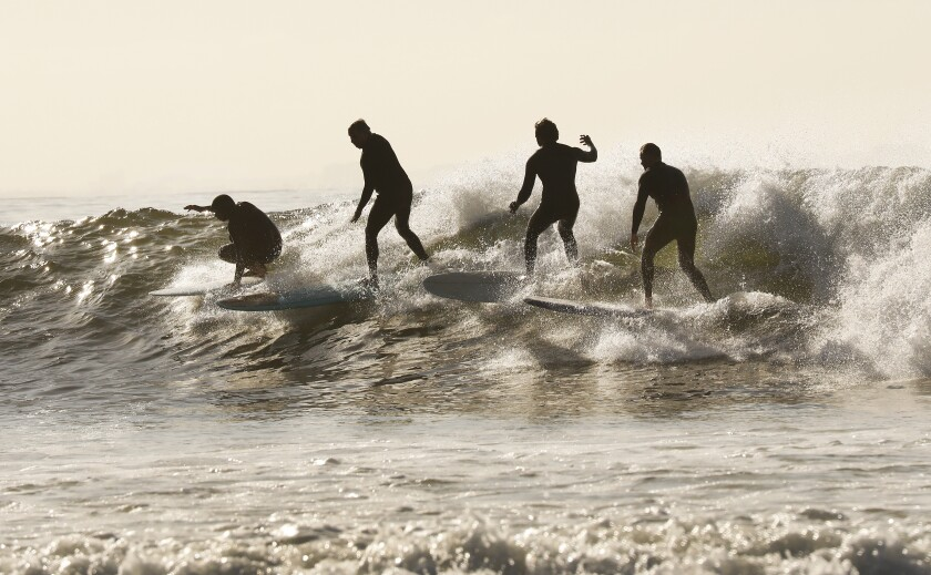 Surfers take advantage of the low tide swell at Malibu Surfrider Beach as Los Angeles County Beaches reopened for active use only.