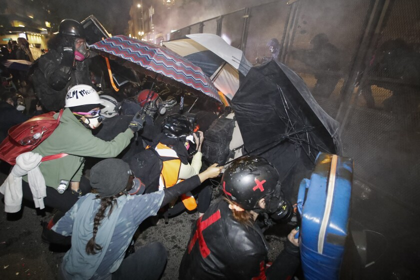 Demonstrators shield themselves with umbrellas as federal officers launch tear gas in Portland, Ore.