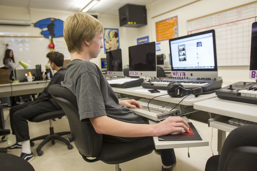 A Huntington Beach High School student works during a media class in 2015. The school is one of nine campuses in the Huntington Beach Union High School District, which is extending its coronavirus-related school closures through April 17.