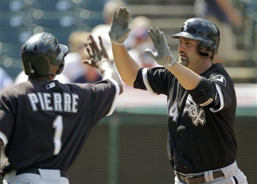 Chicago White Sox's Paul Konerko, right, is greeted by Juan Pierre (1) after hitting a three-run home run off Cleveland Indians relief pitcher Justin Germano in the eighth inning of a baseball game Wednesday, Sept. 1, 2010, in Cleveland. (AP Photo/Mark Duncan)