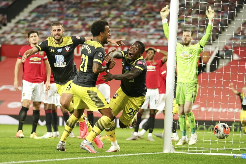 Southampton's Michael Obafemi, centre,celebrates after scoring his team's second goal during the English Premier League soccer match between Manchester United and Southampton at Old Trafford in Manchester, England, Monday, July 13, 2020. (AP Photo/Dave Thompson,Pool)