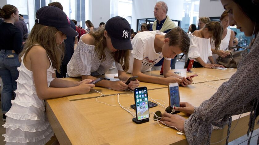 FILE- In this Aug. 2, 2018, file photo customers browse in an Apple store in New York. Apple's iPh