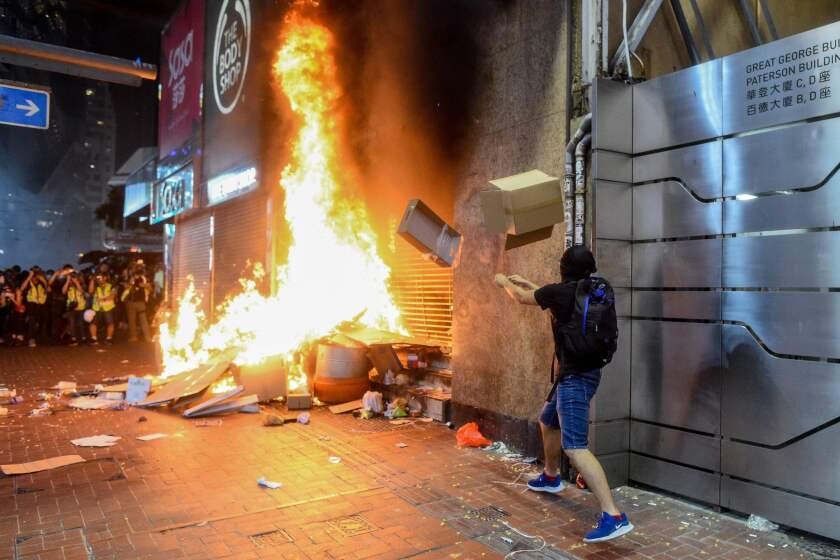 Protesters burn items at the Causeway Bay metro station entrance in Hong Kong, as people hit the streets after the government announced a ban on face masks.