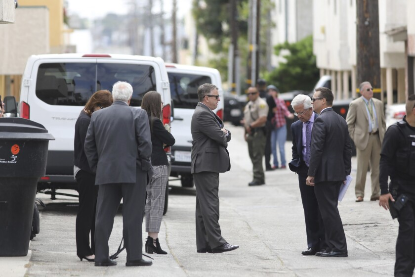 Attorneys and law enforcement officers stand in an alley while jury members visit an evidence site l