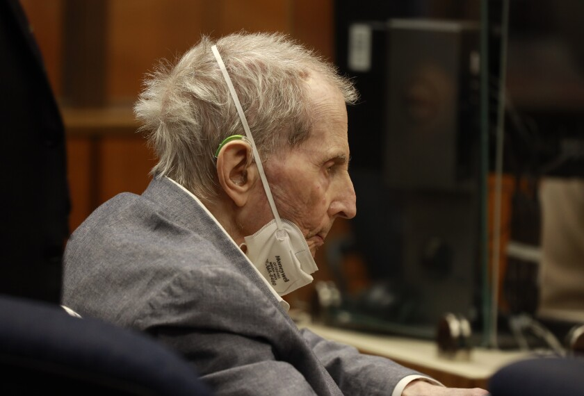 Robert Durst looks down with a mask around his chin while sitting in court