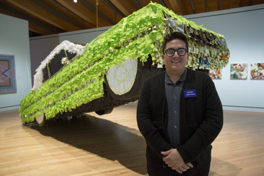 "This Sept. 11, 2014 photo supplied by Crystal Bridges Museum of American Art shows artist Justin Favela with his piece ""Lowrider Pinata"" at the opening for a new show at the museum called ""State of the Art,"" in Bentonville, Ark. The show includes more than 200 works of contemporary art by under-recognized artists. (AP Photo/Crystal Bridges/Marc Henning)"