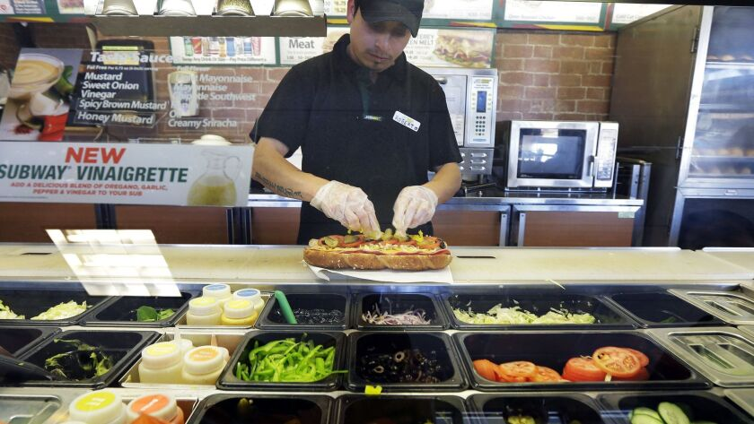 Roberto Castelan makes a sandwich at a Subway sandwich franchise in Seattle in 2015. Some Subway franchise owners say the $5 Footlong promotion loses money for them.