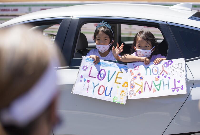 """Abigail and Elia Choi, 5, hold signs and wave to staff members at Mariners Christian School during """"The Great MCS Drive-Bye,"""" a socially distanced celebration on the last day of school on Friday."""