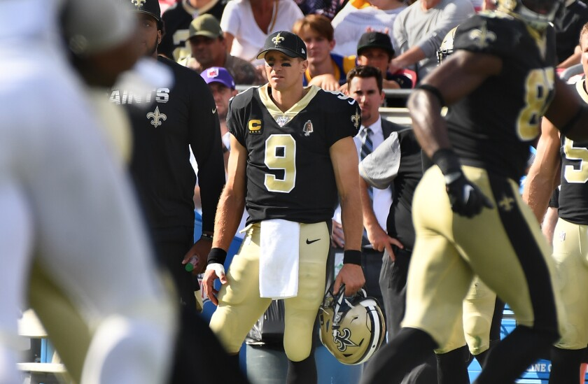 With his thumb wrapped, Saints quarterback Drew Brees watches from the sideline at the Coliseum on Sunday.