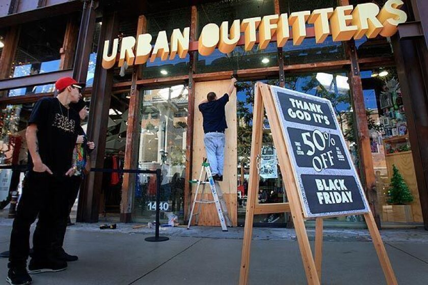 Mike Cruz replaces a glass door broken by Black Friday shoppers as they all tried to squeeze all at once into the Urban Outfitters store on Third Street Promenade. There were minor injuries reported at the scene in Santa Monica.