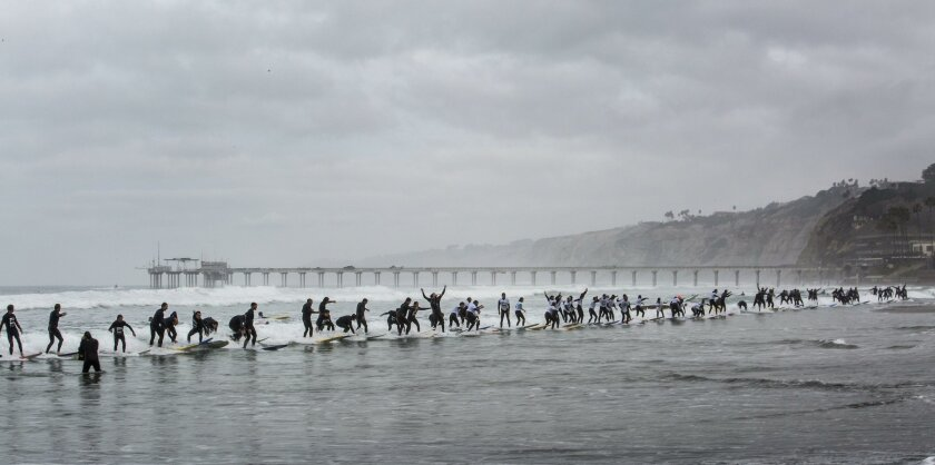 A group of 150 surfers make one of 18 attempts at La Jolla Shores during the One Wave Challenge to ride a single wave for a minimum of five seconds in an attempt to break the Guinness World Record, currently set at 110. The event benefits the Boys to Men in-school mentoring program.