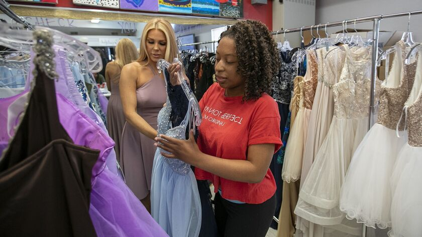Gretchen Rossi helps Jasmine Wilson, 17, find a prom dress at Girls Inc. of Orange County Monday, Ap