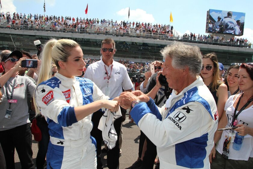 Lady Gaga and Mario Andretti do a double fist-bump before they take a lap in the two-seater IndyCar before the 100th running of the Indianapolis 500, Sunday, May 29, 2016 in Indianapolis.  (Kerry Keating/The Indianapolis Star via AP)  NO SALES; MANDATORY CREDIT