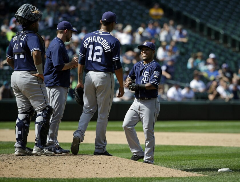 San Diego Padres shortstop Alexi Amarista, right, arrives at the mound to relieve Padres catcher Christian Bethancourt (12), who was pitching in the eighth inning of a baseball game against the Seattle Mariners, Tuesday, May 31, 2016, in Seattle. Amarista finished the inning and the Mariners beat the Padres 16-4. (AP Photo/Ted S. Warren)