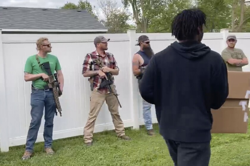 This June, 1, 2020, image from video provided by Alissa Murray shows demonstrators protesting police brutality and racism encountering a line of armed bystanders as they march in Crown Point, Ind. Crown Point Police Chief Pete Land said the armed bystanders are protected under state law. (Alissa Murray via AP)