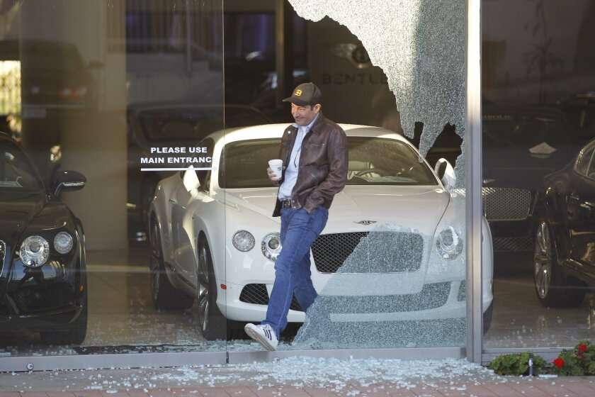 Dealership owner Marc Chase walks through the window of his business that was smashed by burglars Monday morning.