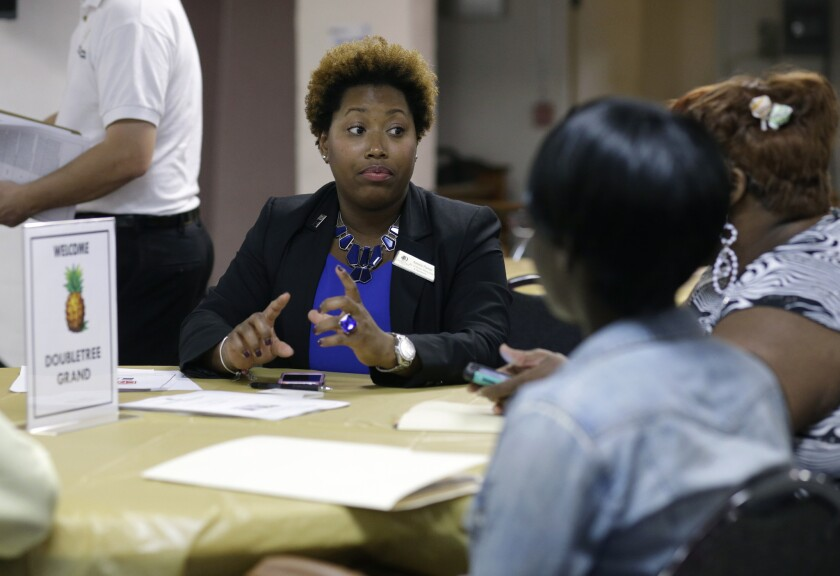 Natalie Parker, director of human resources at the Doubletree Grand in Miami, left, talks with job applicants during a job fair at the Hospitality Institute on Jan. 23.