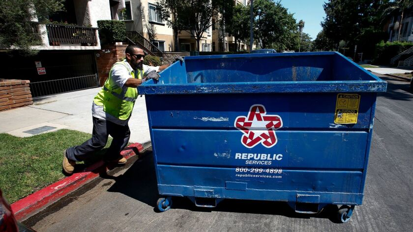 An employee with a private refuse collector, shown in August, moves a bin to the street in West Los Angeles. City officials say the number of complaints generated by their commercial refuse program is dropping.