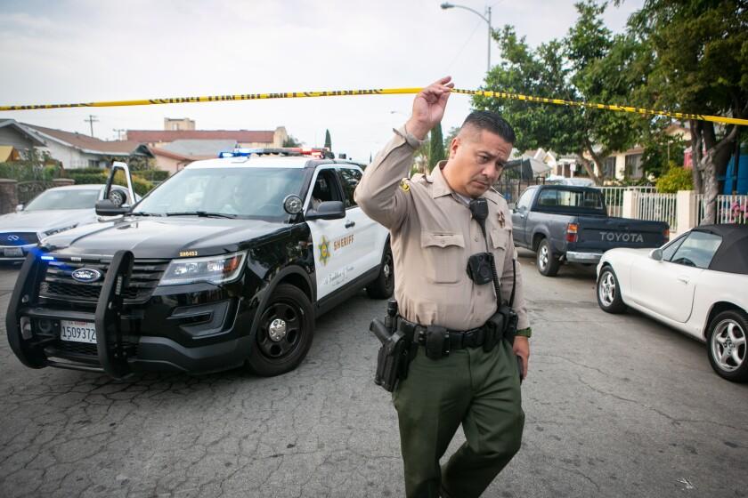 A sheriff's deputy ducks under crime scene tape in East Los Angeles