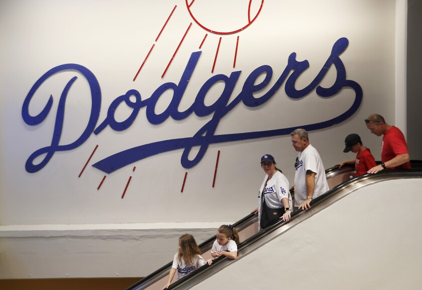 Dodgers fans take an escalator to the field level of Dodger Stadium before the game.