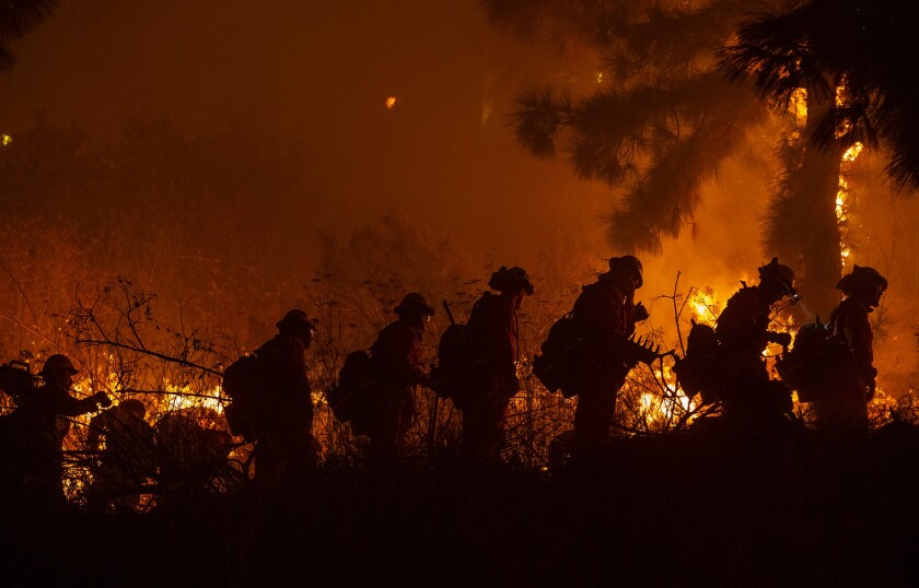 Firefighters head out for brush work in the Sepulveda Pass during the Getty fire