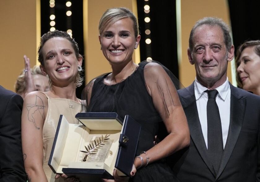 Two women, left, hold an award, and a man stands next to them