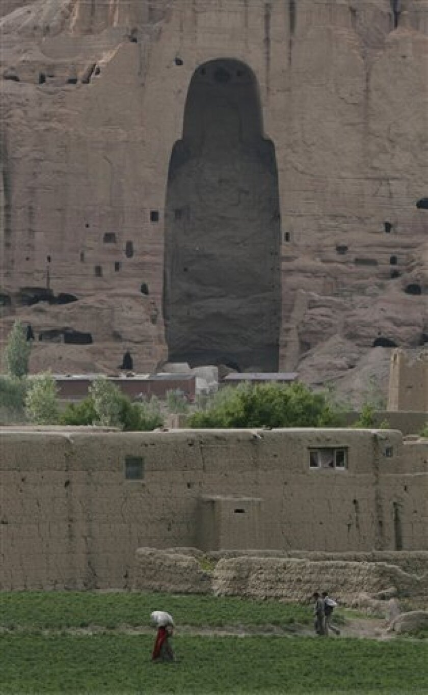 In this photo taken Wednesday, June 17, 2009, people walk past the cliffs that once held giant Buddhas destroyed by the Taliban in 2001 in Bamiyan, central Afghanistan. In an attempt to return one small part of the country to normalcy government officials and international donors are promoting tour