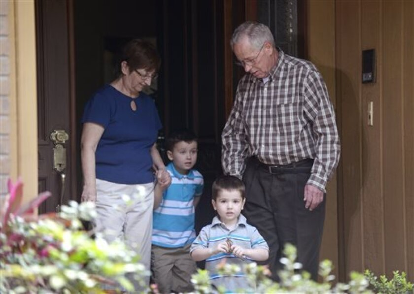 Patricia and Robert Hauser escort their grandchildren, Chase Hakken, 2, second from right, and Cole, 4, out of their house to speak to the media in Tampa, Fla., Thursday, April 11, 2013. The boys were returned to the Hausers, who have legal custody of them, after their parents, Joshua and Sharyn Ha