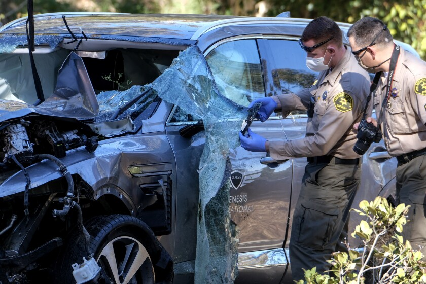 Law enforcement officers look over the SUV Tiger Woods crashed in Rolling Hills Estates.