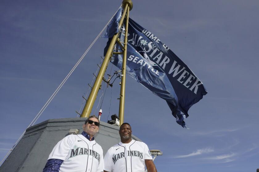 Los peloteros retirados Édgar Martínez (izquierda) y Ken Griffey Jr. posan para las fotos después de izar una bandera del Juego de Estrellas en la torre Space Needle, el jueves 16 de septiembre de 2021 (AP Foto/Ted S. Warren)