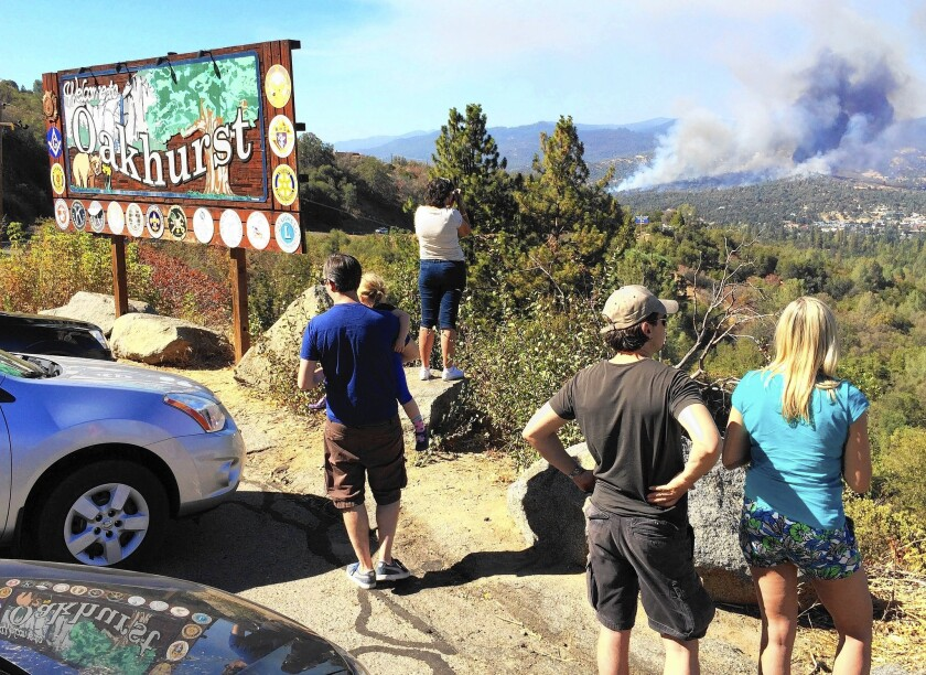 People watch a fire burning from the California 41 overlook on the way north into Oakhurst, Calif.