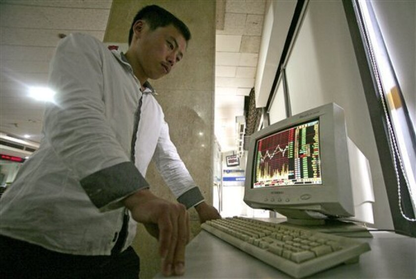 An investor looks at stock price monitor at a private securities company Tuesday, June 8, 2010 in Shanghai, China. Asian stock markets are mostly higher Tuesday after Federal Reserve Chairman Ben Bernanke indicated the U.S. economy was still on the mend and the European common currency stabilized after hitting a new four-year low against the dollar. (AP Photo)