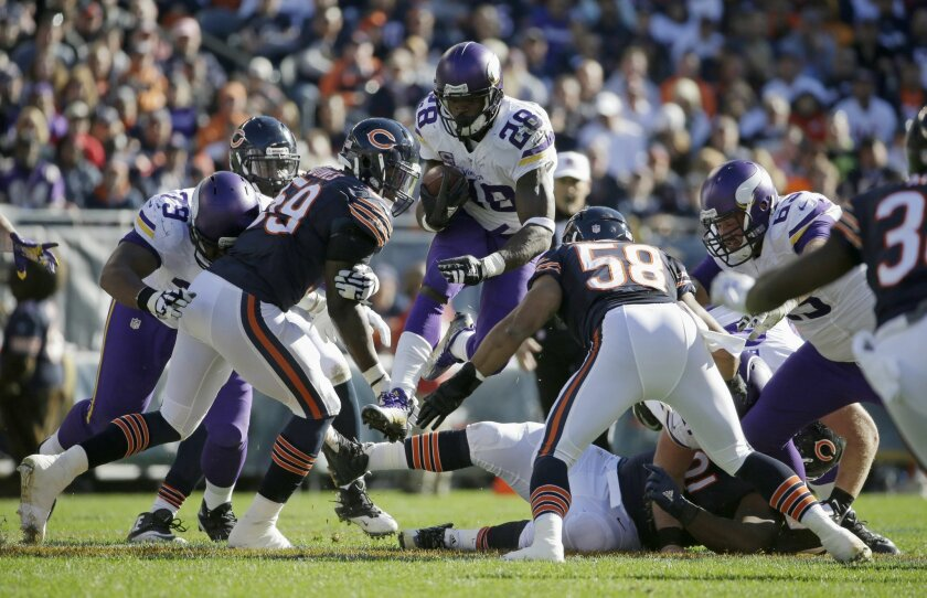 Minnesota Vikings running back Adrian Peterson (28) leaps over players as he carries the ball against Chicago Bears defenders during the first half of an NFL football game, Sunday, Nov. 1, 2015, in Chicago. (AP Photo/Nam Y. Huh)