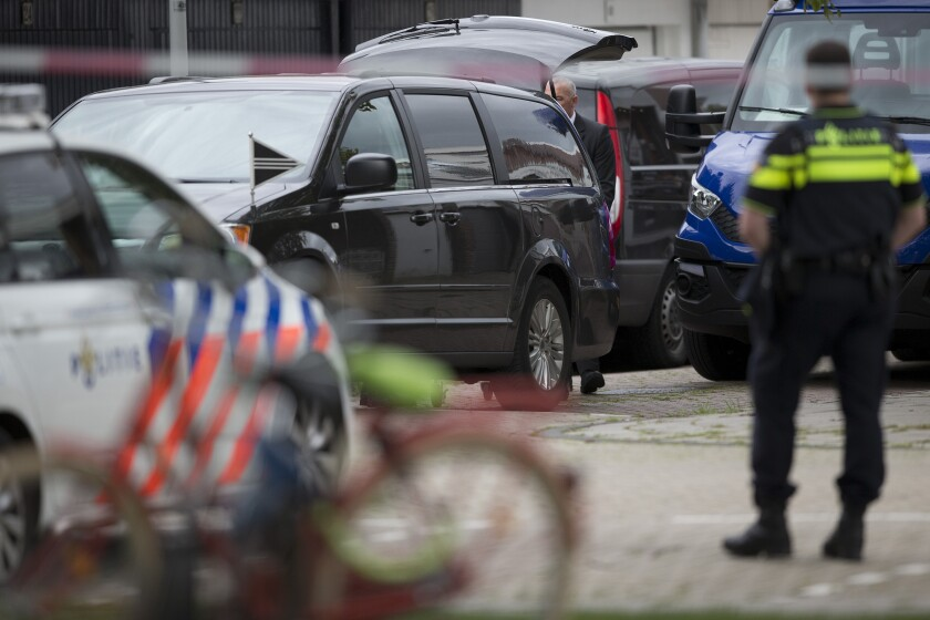 FILE - In this Wednesday, Sept. 18, 2019 file photo, the body of a lawyer who represented a key witness in a major Dutch organized crime trial is carried into a hearse after he was gunned down in Amsterdam, in Amsterdam, Netherlands. Two men were convicted Monday, Oct. 11, 2021, and sentenced to 30 years for the murder of a Dutch lawyer who represented a witness in a high-profile criminal case against suspected gangland bosses, a slaying that shocked the nation and sparked calls for a tougher crackdown on organized crime. (AP Photo/Peter Dejong, file)