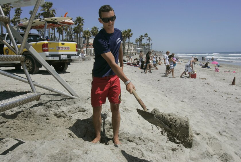 Oceanside seasonal lifeguard Sam Hoover uses a shovel to build up a sand ramp for easier access to his tower near the Oceanside Pier. He's expecting it to be busy this weekend.