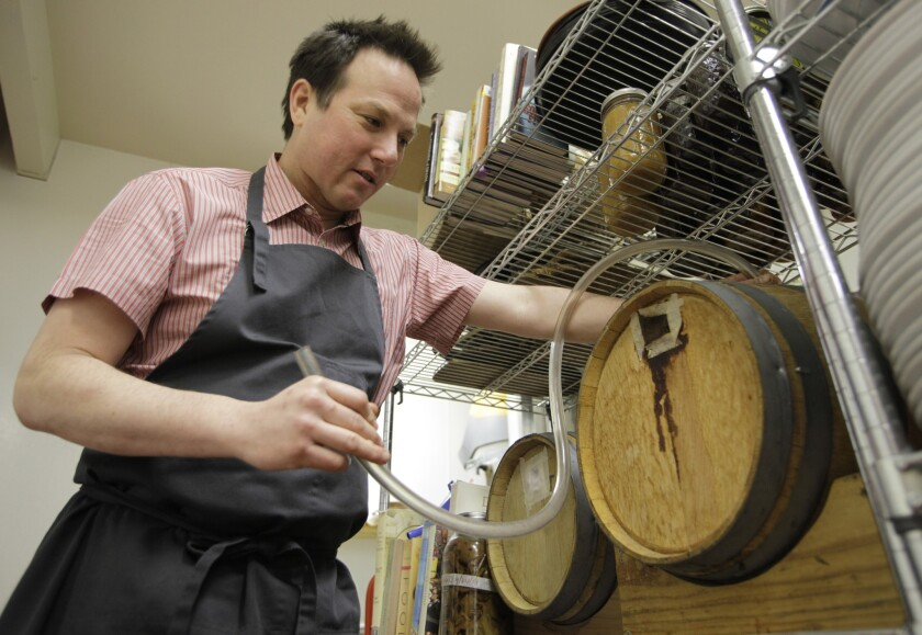 FILE– This Thursday, Feb. 24, 2011 file photo shows chef Russell Moore as he poses next to barrels t