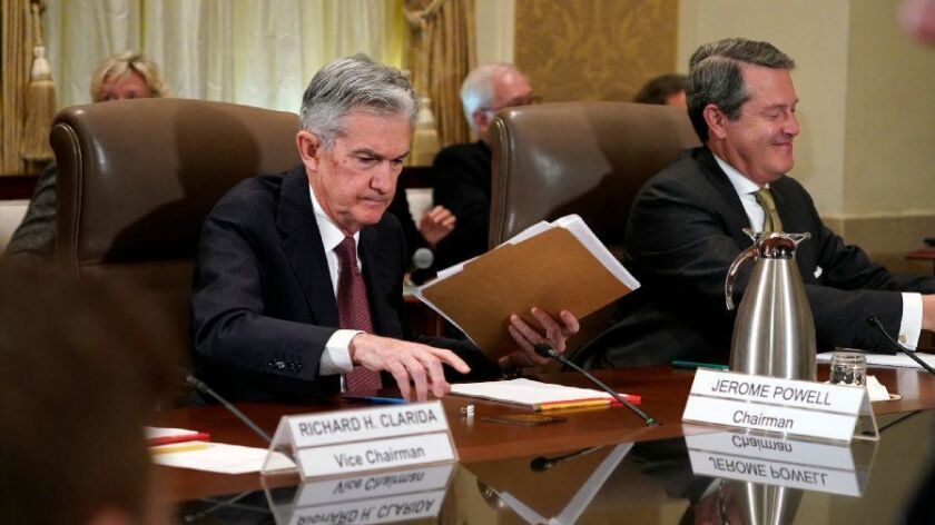 Federal Reserve Chairman Jerome Powell, left, and Randal Quarles, vice chairman for supervision, gather their things at the end of an Oct. 31, 2018, Fed board meeting in Washington. On Nov. 8, the Federal Reserve left its key policy rate unchanged.