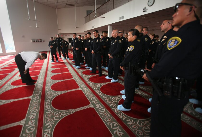 Imam Sheik Abdel Jalil, left, demonstrates to police officers the posture for prayer they might see at the mosque or even in public.  San Diego Police Department's newest police officers had barely graduated from the academy Friday visited various community centers, starting with the Islamic Cen