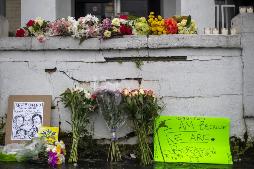 Flowers and signs are displayed at a makeshift memorial outside of the Gold Spa in Atlanta, Wednesday, March 17, 2021.