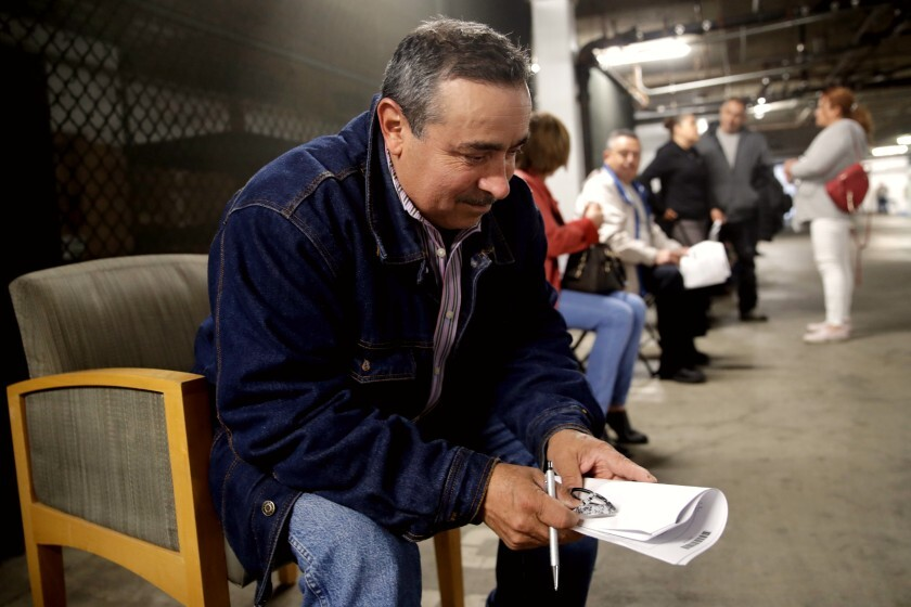 Luis Estrada waits in line in a basement garage to apply for unemployment benefits.