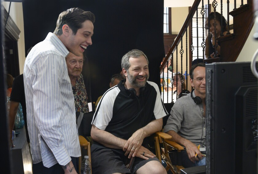 "In this image released by Universal Pictures, Pete Davidson, left, appears with director Judd Apatow, center, during the filming of ""The King of Staten Island."" (Mary Cybulski/Universal Pictures via AP)"