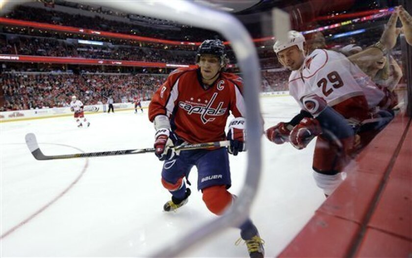 Washington Capitals left wing Alex Ovechkin (8), from Russia, goes for the puck with Carolina Hurricanes right wing Tim Wallace (29) nearby, during the second period of an NHL hockey game Tuesday, March 12, 2013 in Washington. (AP Photo/Alex Brandon)