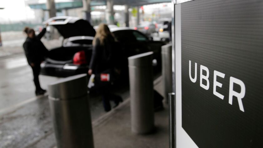 A sign marks a pickup point for the Uber service at LaGuardia Airport in New York.