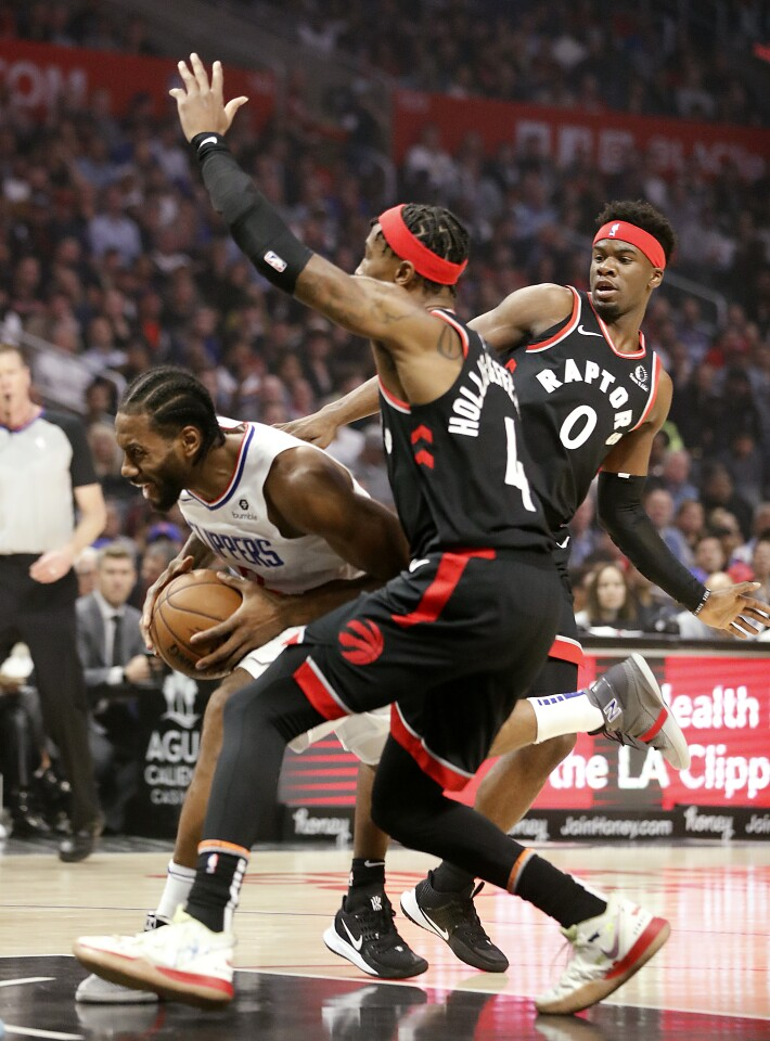 LOS ANGELES, CALIF. - NOV. 11, 2019. Clippers forward Kawhi Leonard splits the defnse of Raptors Rondae Hollis-Jefferson and Terence Dsvis II in the first quarter at Staples Center in Los Angeles on Monday night, Nov. 11, 2019. (Luis Sinco/Los Angeles Times)