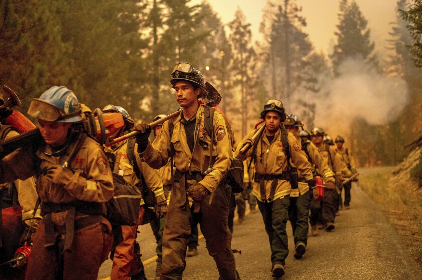Firefighters march down a mountain road