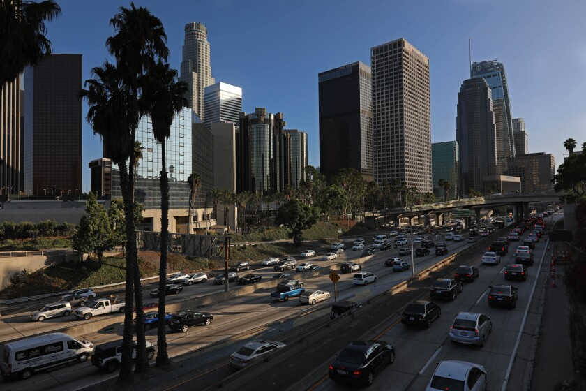 A view of freeway lanes filled with cars, palm trees in the foreground and tall buildings in the background.