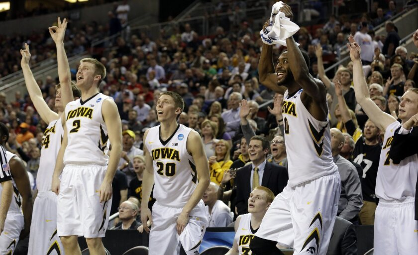 Iowa players react from the bench to a three-point score against Davidson late in the second half of an NCAA tournament college basketball game in the Round of 64 in Seattle, Friday, March 20, 2015. Iowa won 83-52. (AP Photo/Elaine Thompson)