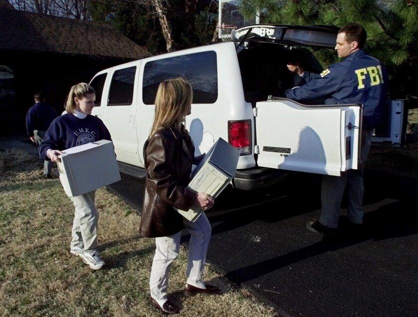 FBI agents load computers taken from the home of FBI agent Robert Philip Hanssen into an agency vehicle in Vienna, Va., on Feb. 20, 2001.
