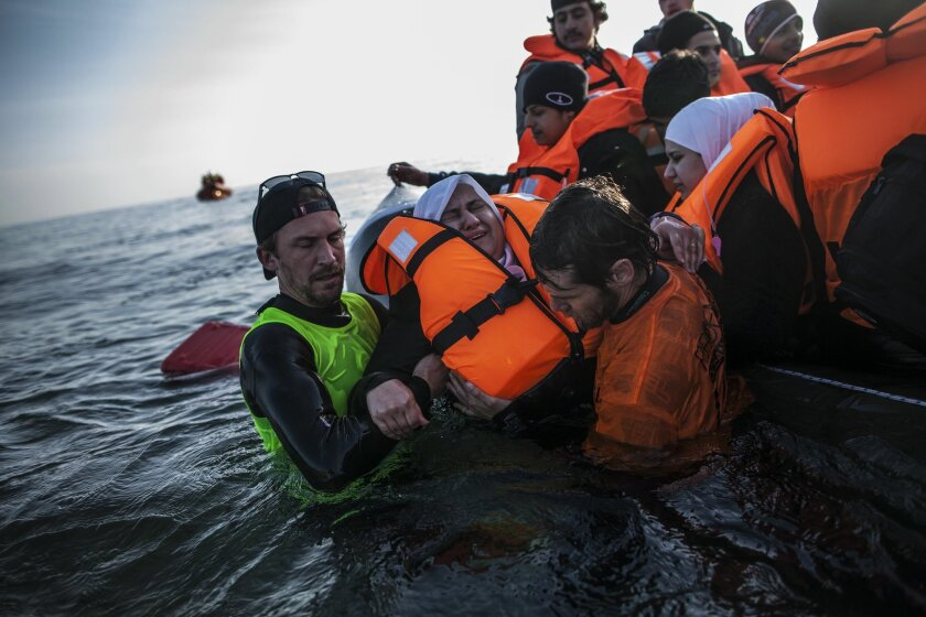 A Syrian refugee is helped by volunteers to leave a sinking dinghy at a beach on the southeastern island of Lesbos, Sunday, Feb. 28, 2016. Greece is mired in a full-blown diplomatic dispute with some EU countries over their border slowdowns and closures. Those border moves have left Greece and the migrants caught between an increasingly fractious Europe, where several countries are reluctant to accept more asylum-seekers, and Turkey, which has appeared unwilling or unable to staunch the torrent of people leaving in barely seaworthy smuggling boats for Greek islands. (AP Photo/Manu Brabo)